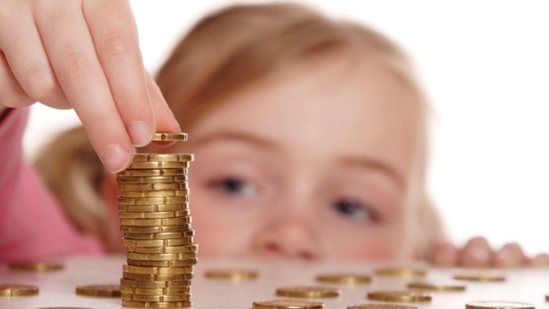 Ребенок строит пирамидку из монет